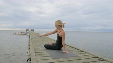 медитация : Beautiful young girl making yoga pose on the old wooden pier at the sea. Exercises calmness and harmony. Стоковые видеозаписи