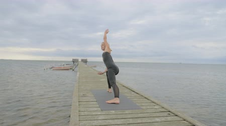 Beautiful young girl making yoga pose on the old wooden pier at the sea. Exercises calmness and harmony. Stockvideo