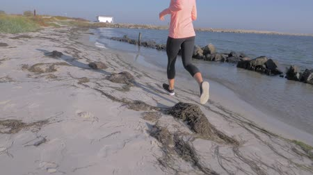 утро : Slow motion young woman jogging along the sea coast