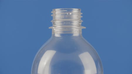 biodegradable : Recyclable plastic bottle spinning against a blue background. Close up