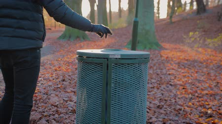 discard : man throws trash in a trash bin in a park on a sunny autumn day