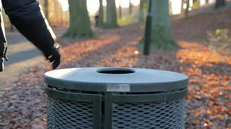 барахло : man throws trash in a trash bin in a park on a sunny autumn day