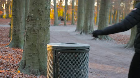 crumpled : man throws trash in a trash bin in a park on a sunny autumn day