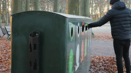 discard : man throws trash in a recycling station in a park a sunny autumn day Stock Footage