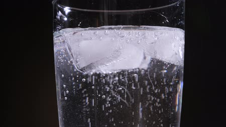 aerated : Close up of a refreshing cold drink with bubbles. Ice Cubes drop down sparkling water.