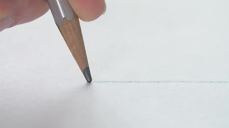 grafite : Close-up of artists drawing a straight line with a wooden pencil on white paper.