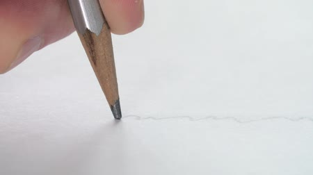 grafit : Close-up of artists drawing a wavy line with a wooden pencil on white paper. Stok Video
