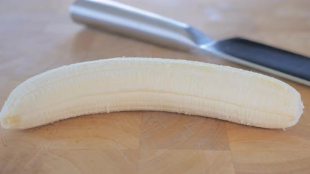 savanyú : Close-up of a peeled banana and a knife on cutting board. Sliding motion