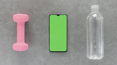 calorias : Green screen - A Smartphone, water bottle and a dumbbell lying on a gray stone table. Top view.