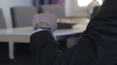punctuality : Male businessman looks at his watch to tell the time while he is waiting for a meeting. close up Stock Footage