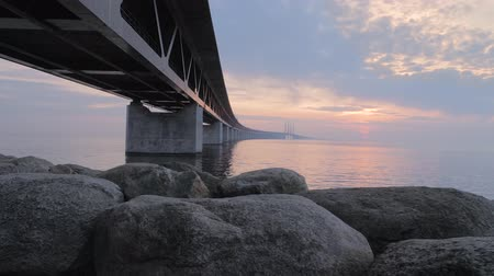 escandinavo : Oresundsbron at sunset. The bridge between Sweden and Denmark. Camera movement along the stones at the bridge