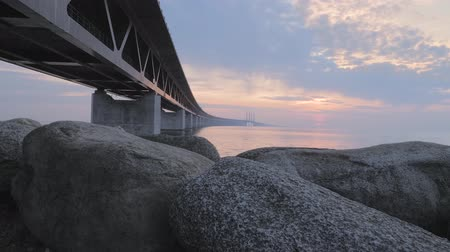 İskandinavya : Oresundsbron at sunset. The bridge between Sweden and Denmark. Camera movement up along the stones revealing the bridge