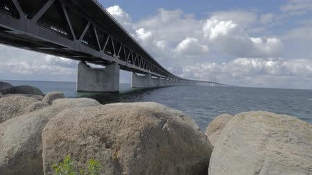 escandinavo : Oresundsbron with blue sky and white clouds. The bridge between Sweden and Denmark. Camera movement up along the stones revealing the bridge