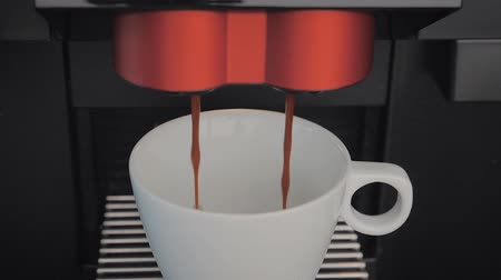 porselen : slow motion: highest quality coffee made with a professional coffee machine falls into a porcelain coffee cup in slow motion.
