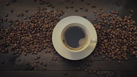 italian coffee : Coffee cup and coffee beans on a black wooden table. Sliding motion and top view. Stock Footage