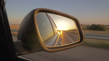 side road : Close-up of the side view car mirror at sunset. Car drives on the highway
