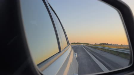 side window : Close-up of the side view car mirror at sunset. Car drives on the highway