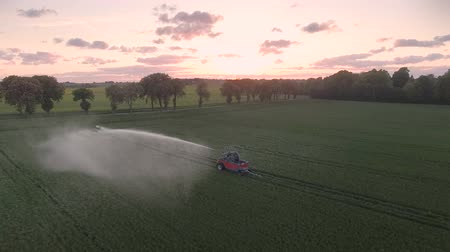 Drone view: water cannon standing in a field at sunset. Colorful sky with clouds