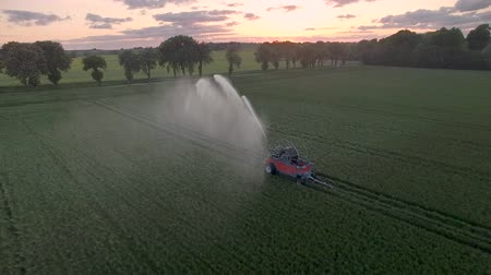 water cannon : Drone view: water cannon standing in a field at sunset. Colorful sky with clouds