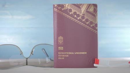 Swedish EU Passport. Dolly movement along sunglasses, passport, and a toothbrush Stockvideo