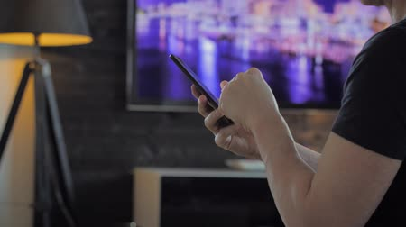 Man sitting in a modern living room scrolling and using gestures on a smartphone. Tv in the background
