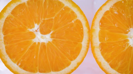 spraying : Sliding along oranges slices on a white and wet background. Close up Stock Footage