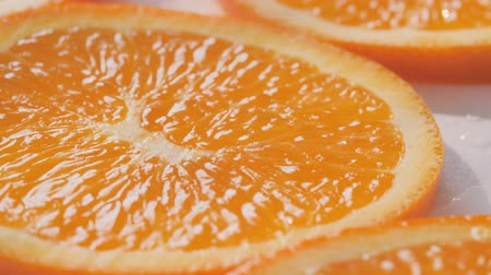 rough skin : Sliding along oranges slices on a white and wet background. Close up Stock Footage