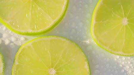 compelling : Sliding along lime slices on a white and wet background. Close up