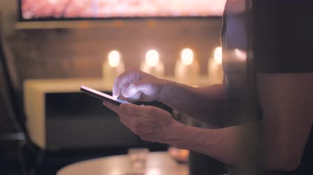 Close up of a man sitting in a modern living room scrolling and using gestures on a smartphone. Sliding motion. Stockvideo