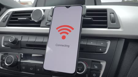 a smart phone on the dashboard of a car connects to wifi. Sliding motion Stockvideo