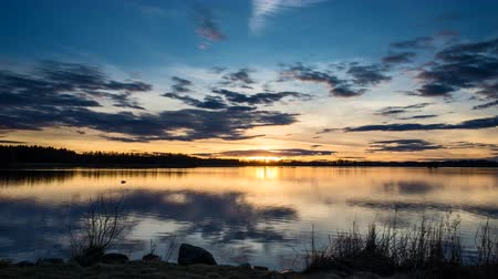 Швеция : Sunset at lake in Sweden Europe. Beautiful nature and landscape time lapse on spring evening. Lovely colorful sky and reflection in water. Nice, peaceful, calm and happy outdoors movie.