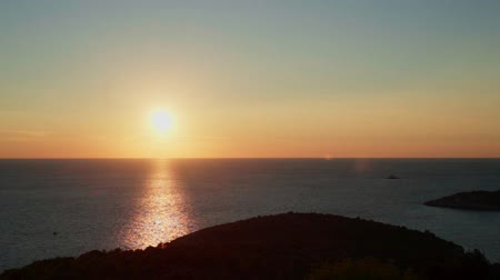 dalmácia : Sunset at Adriatic Sea Croatia. Beautiful nature and landscape video of sun low at horizon over sea. Nice reflections in water. Calm, peaceful, joyful and happy outdoors evening at dalmatia coast. Stock mozgókép