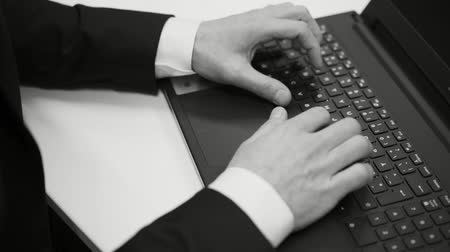 levelezési : Black and white movie of male caucasian businessman sitting at desk typing on laptop computer, Close up of hands and fingers Stock mozgókép