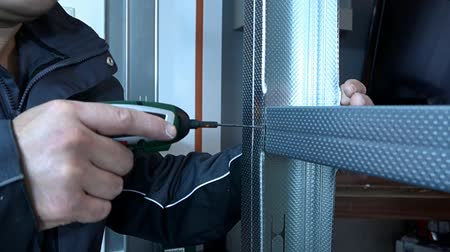 locksmith : Repairs in the apartment. The man twists the screw profile.