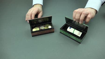 compares : The man puts on a gray table two stone boxes and compares the accumulation of money. In one box accumulation were different coins and in banknotes.