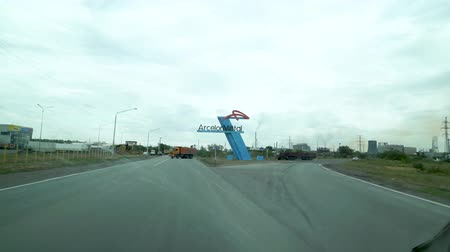 associados : The road before entering the city of Temirtau, Kazakhstan. On the right side stands the emblem of the metallurgical plant Arcelor Mittal.