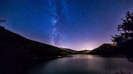 lapse : night sky stars timelapse. milky way on mountain lake landscape