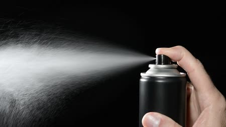 pulverização : A man depresses the button on an aerosol spray can, dispensing chemicals into the atmosphere
