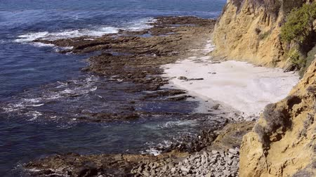 Калифорния : A cliff side view of a very rugged part of the pacific coast shore in California shows the sharp reef, deep blue water and isolated white sandy beach.