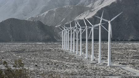 obnovitelný : A row of windmills turning with the wind generate power for a local community.