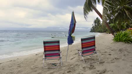 impending : Two beach chairs and an umbrella sit on a tropical beach during an impending storm Stock Footage