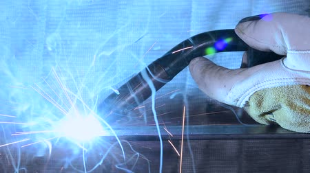 soldagem : A metal worker welds a piece of steel, generating blue flames and sparks Vídeos