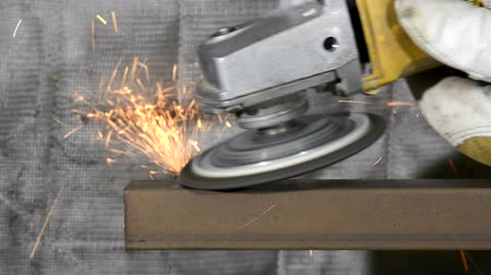 żelazko : A metal worker uses a grinding wheel to shave off some steel from square stock Wideo