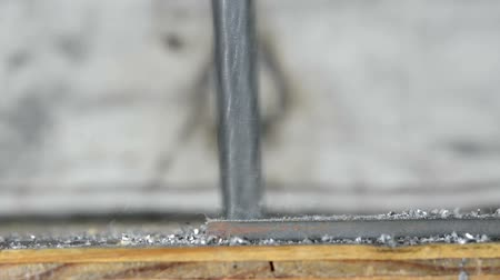 broca : A drill bit cutting into a piece of metal backed by wood shows the heat and chips flaking off