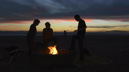 şenlik ateşi : Friends gathered around a beach fire pit during a beautiful sunset cooking marshmallows