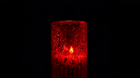 láng : A burning candle in a red holder is blown out, producing a smoky scene