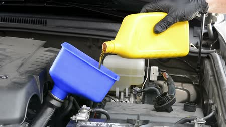 změna : A mechanic pours fresh, clean oil into a car engine during routine automobile maintenance.