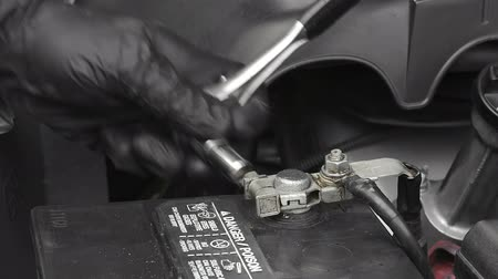 csavarkulcs : A mechanic cleans a battery terminal with a wire battery terminal brush during routine automobile maintenance.  Stock mozgókép