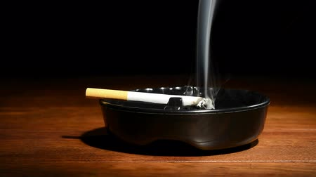 hamu : A burning cigar in a classic black ashtray streaming smoking in a dark, moody setting. Shot with a Nikon D7100 24MP camera at f7, 30 shutter speed.