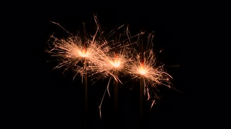 освещенный : Three burning gold firework sparklers emitting sparks against a black background.